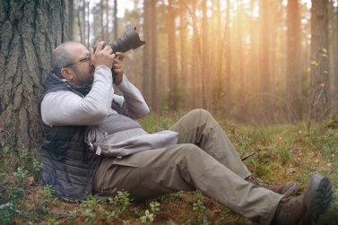 Mature Adult man walking in the woods and take pictures